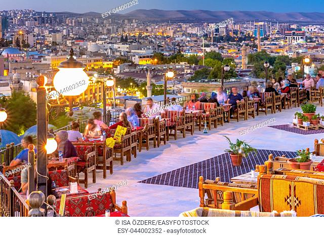 Unidentified sit a terrace cafe over Golbasi Park to watch sunset Sanliurfa,Turkey. 18 July 2018