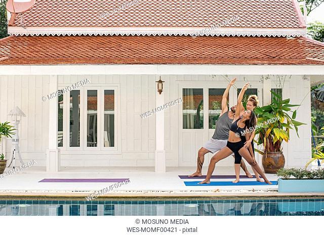Yoga instructor teaching woman correct yoga pose on terrace