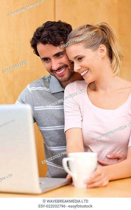 Portrait of a couple using a laptop while having tea