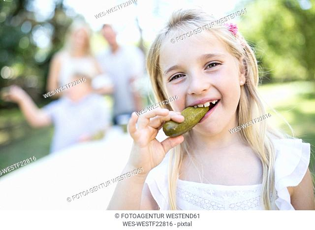 Portrait of girl eating gherkin outdoors with family in background