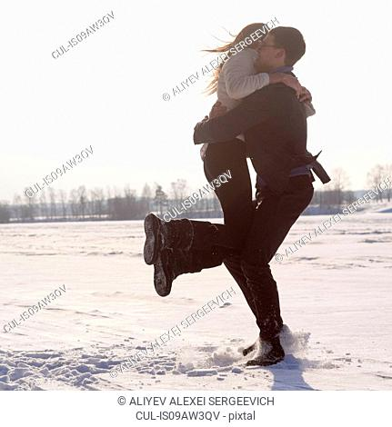 Young man carrying woman on snow-covered field