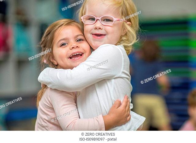 Portrait of two young girls in classroom, hugging