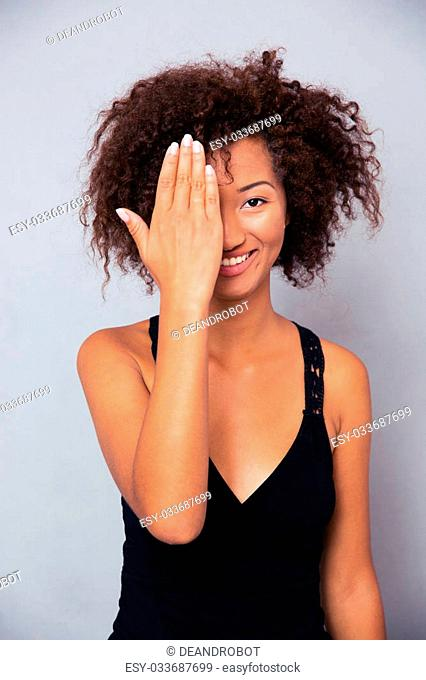 Portrait of a smiling afro american woman covering her eye and looking at camera over gray background