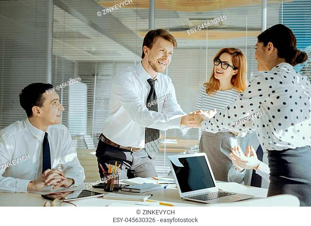 Sincere congratulations. Charming pleasant boss shaking hands with his female colleague, congratulating her on promotion, while the other colleagues cheering