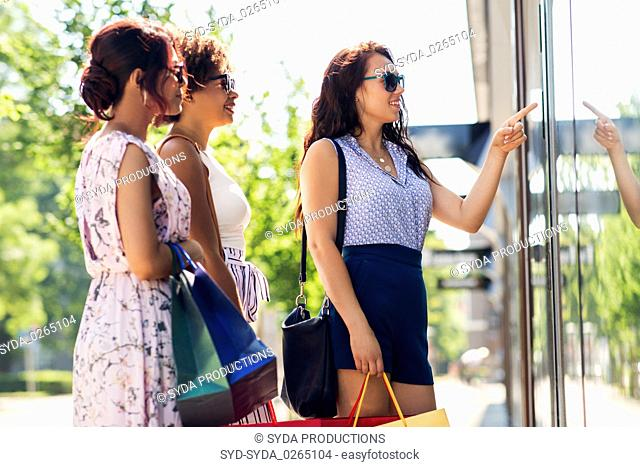 women with shopping bags looking at shop window