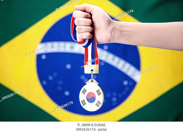 Hand holding a gold medal with Korean flag at Olympic Games