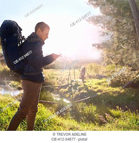 Young man with backpack hiking, checking smart phone in sunny field