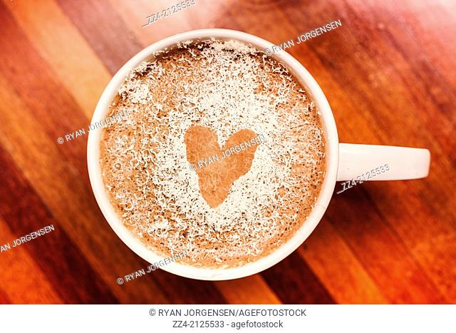 Coffee love with a white coffee cup against a brown wooden background and a heart shape made from the chocolate sprinkles