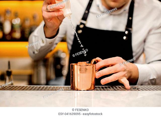 Bartender in a white shirt and black apron pouring alcoholic drink into a metal cup