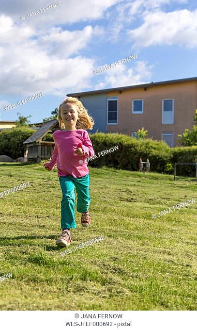 Portrait of smiling little girl running on a meadow