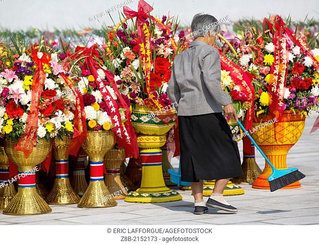 Old Woman Cleaning The Baskets Of Flowers In Front Of The Two Statues Of The Dear Leaders In Grand Monument Of Mansu Hill, Pyongyang, North Korea