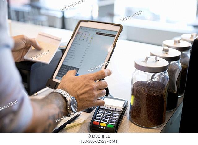 Male cafe owner holding check using digital tablet at cash register