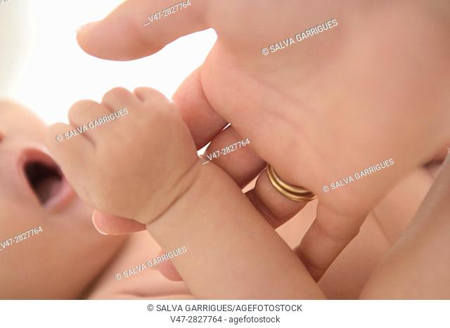 Baby grabs the finger of his mother's hand