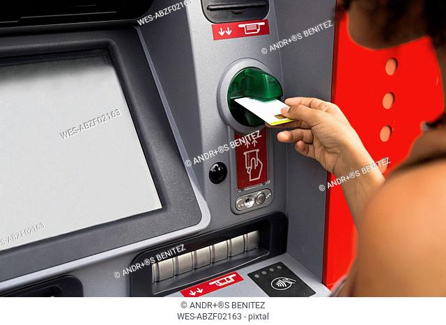 Woman pushing credit card at cash dispenser, partial view