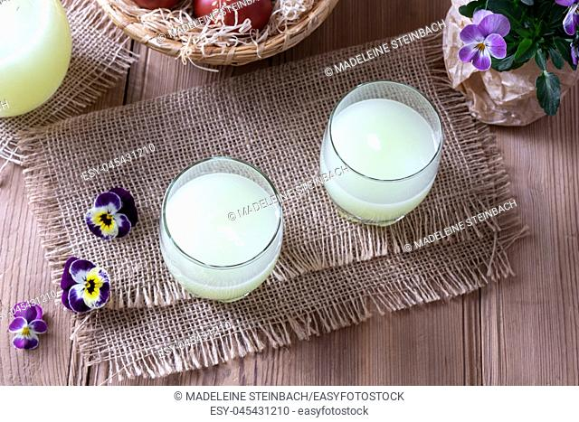 Two glasses of fresh whey and pansy flowers on a table
