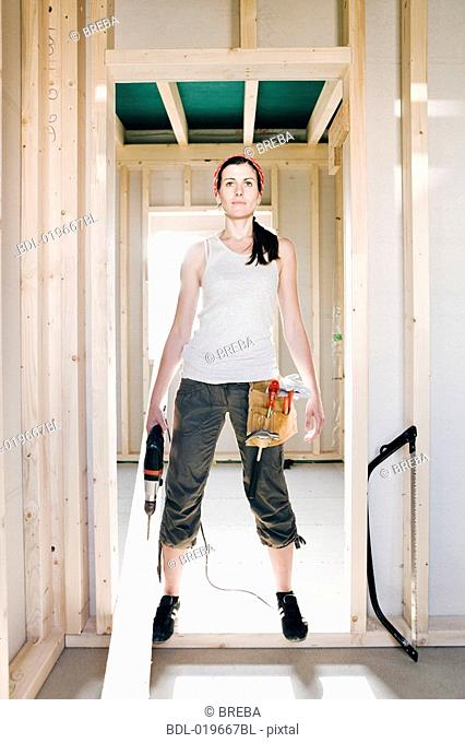 full body portrait of young woman standing in door of house under construction