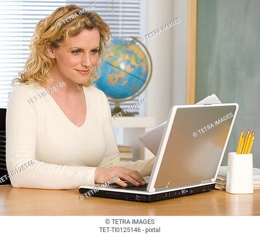 Female teacher typing on laptop