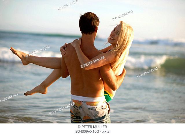 Rear view of man in front of ocean carrying smiling woman