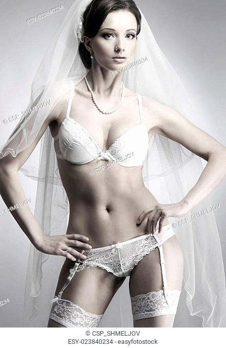 Young sexy bride in erotic lingerie over grey background with a