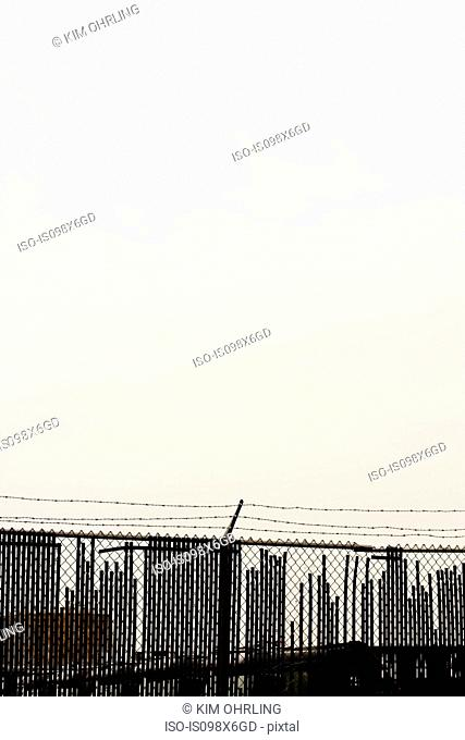 Barbed wire fence and skyline, New York City, New York, USA