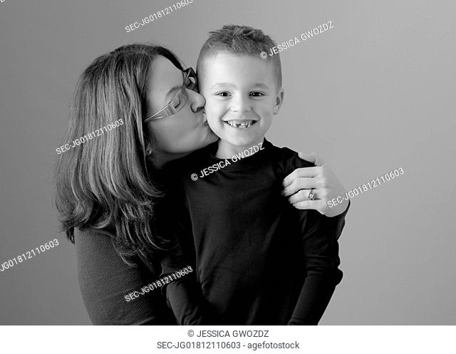 Mother kissing son on cheek