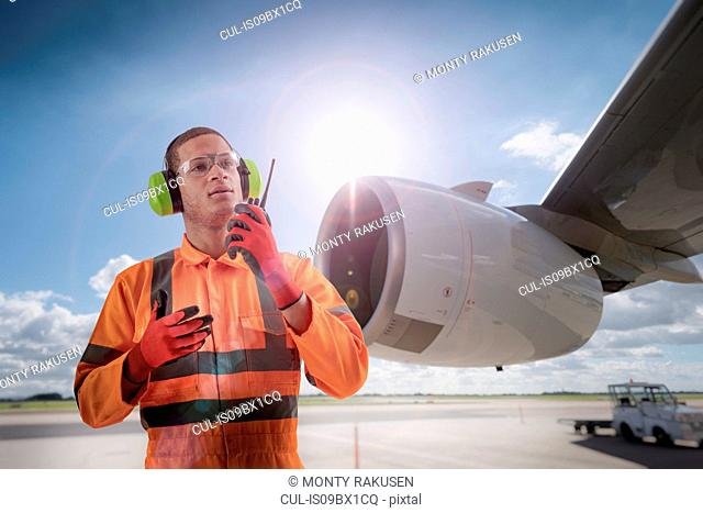 Composite image of airport worker speaking on walkie talkie in front of A380 engine