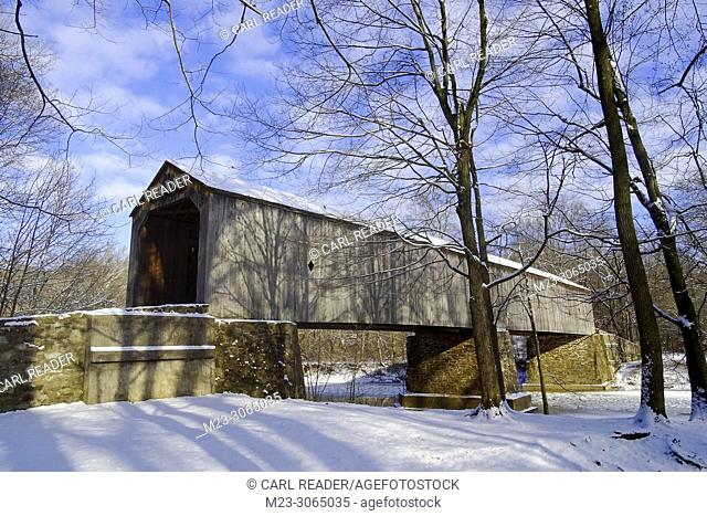 A sideways view of an old wooden covered bridge with snow, Pennsylvania, USA