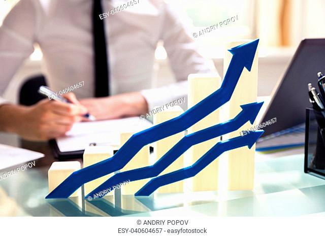 Close-up Of Blue Arrows In Front Of Graph Showing Upward Direction On Desk