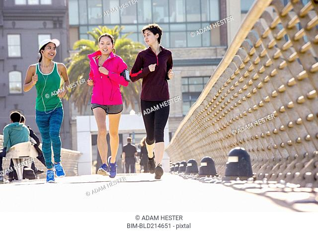 Women running on urban footbridge