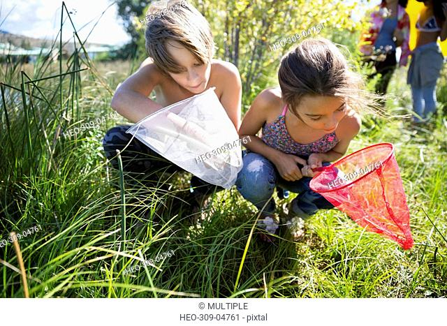 Curious brother and sister looking at fishing nets in sunny grass