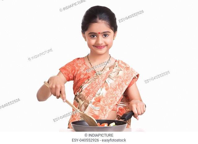 Portrait of little girl dressed as housewife cooking