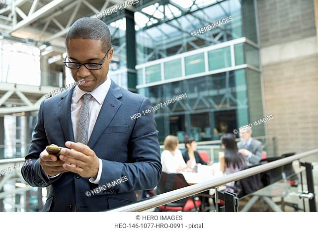 Businessman texting with cell phone outside meeting