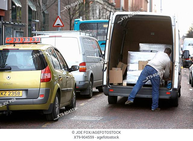 man unloading wrapped pallet boxes from van double parked in the road with traffic going past Belfast Northern Ireland UK