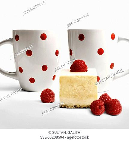 Piece of raspberry cake and two cups