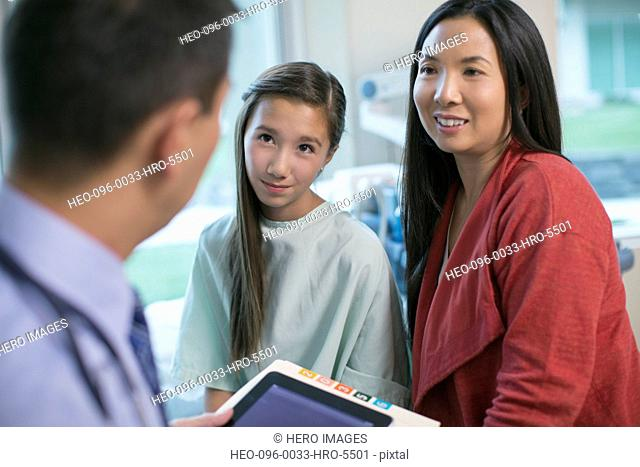 doctor having discussion with teenage daughter and mother