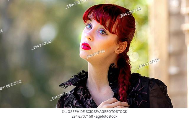 A pretty 23 year old red headed woman looking at the camera, outdoors