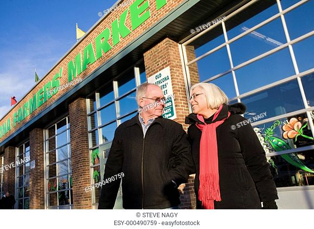 Senior couple outside farmer's market, Old Strathcona, Edmonton, Alberta, Canada