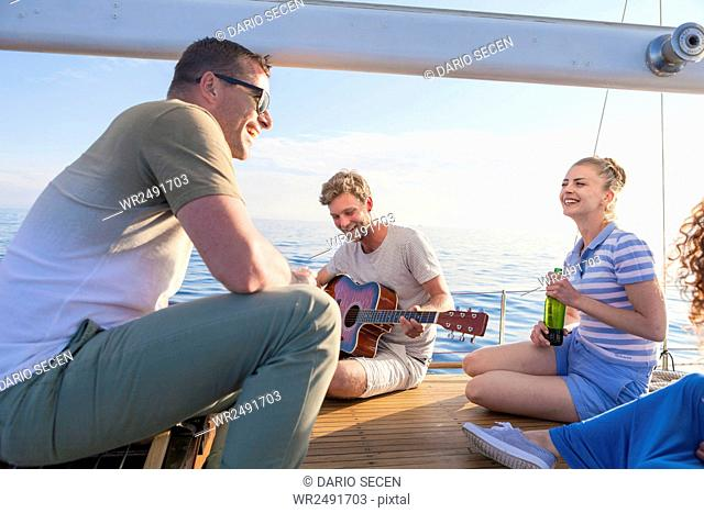 Young man playing guitar on sailboat