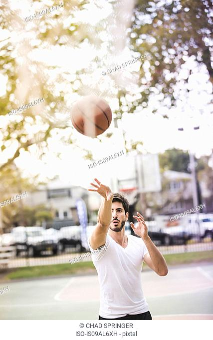 Young male basketball player throwing ball to basketball hoop