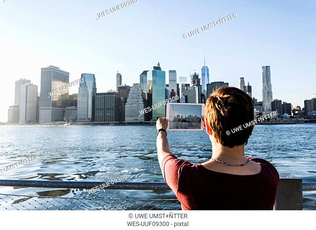 USA, Brooklyn, back view of woman taking picture of Manhattan skyline with tablet