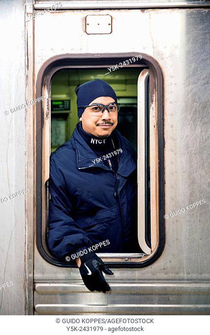 Subway, New York, USA. Male African American conductor looking out de window of a subway train, prior to leaving a subway station