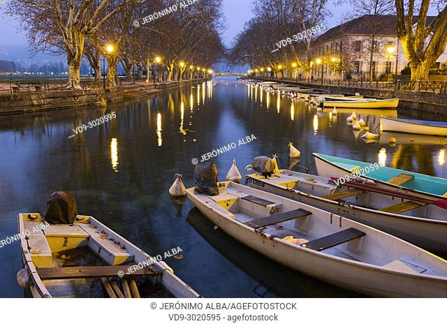 Lac d'Annecy. Wooden rowboats docked along the tree-lined at dusk, Annecy. France, Haute-Savoie, Rhone-Alpes, Europe