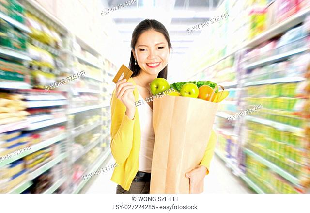 Young Asian woman hand holding shopping paper bag filled with fruits and vegetables and credit card in market or department store