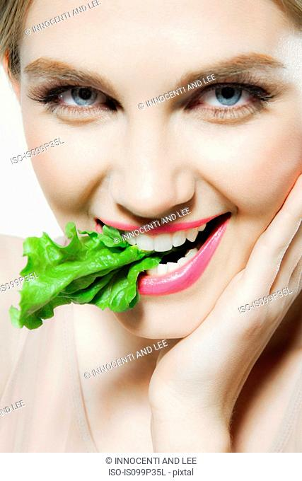 Young woman biting lettuce