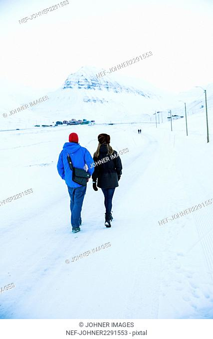 Couple walking on snow-covered road