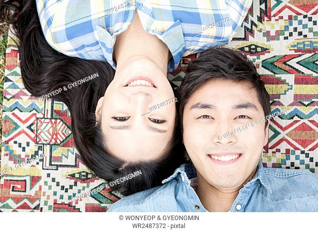 Portrait of young smiling couple lying down