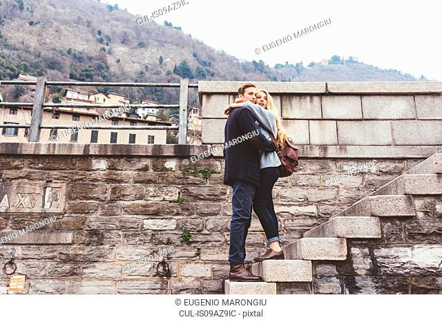 Young couple hugging harbour wall steps, Lake Como, Italy