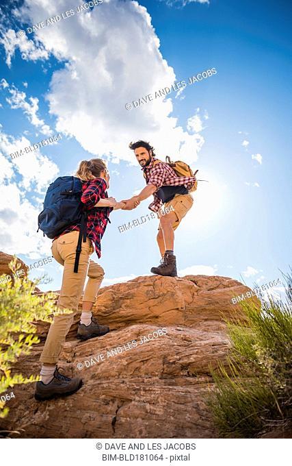 Hispanic couple hiking on hilltop