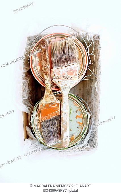 Still life of paint brushes and tins in shoe box