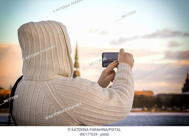 Man in white knitted jacket taking photo of cityscape with his smartphone in Riga, Latvia